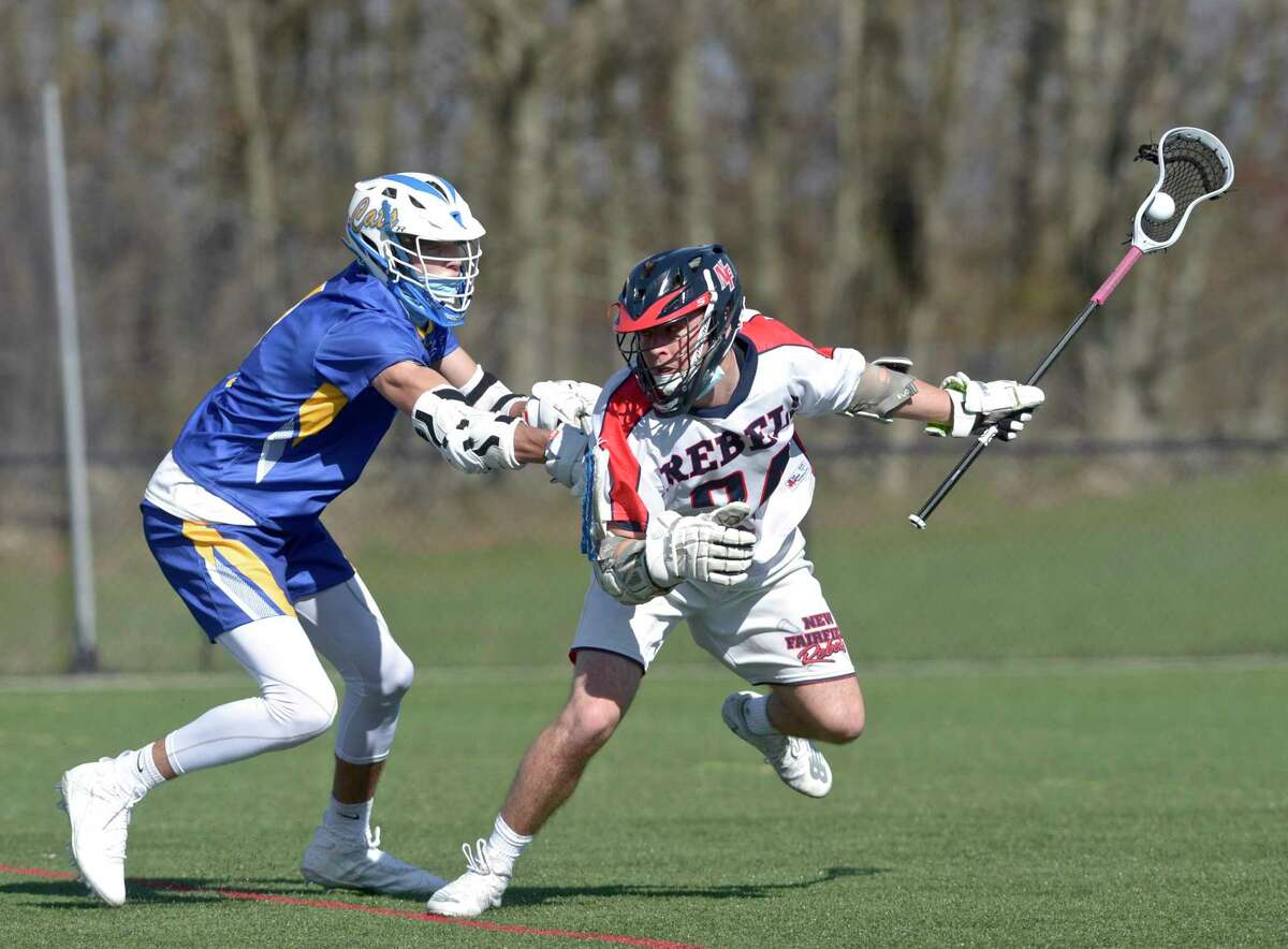 New Fairfield's Matt Constantinides (24) moves with the ball while being defended by Brookfield's Jackson Breuel (7) in the boys lacrosse game between Brookfield and New Fairfield high schools. Tuesday, April 13, 2021, at New Fairfield High School, New Fairfield, Conn.
