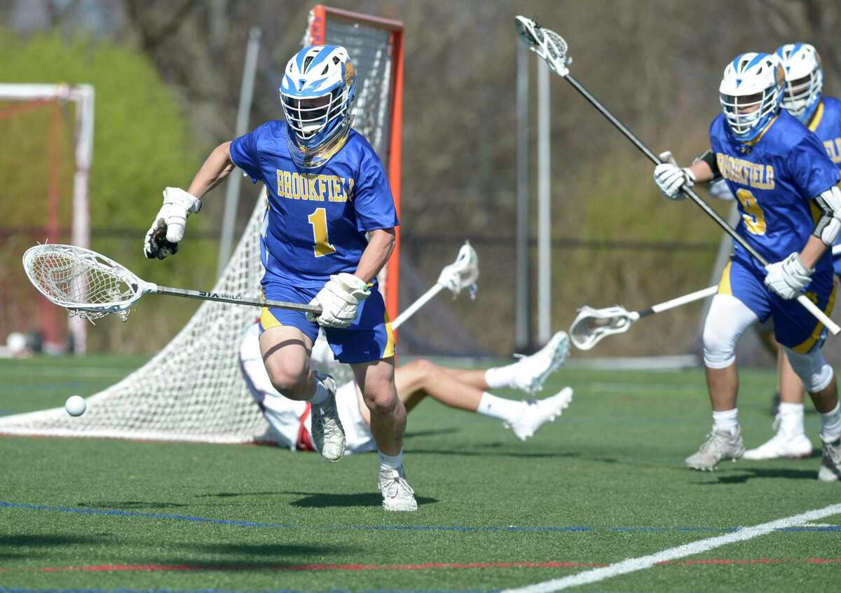Brookfield goalie Nicholas Schilling (1) chases down a loose ball away from the goal in the boys lacrosse game between Brookfield and New Fairfield high schools. Tuesday, April 13, 2021, at New Fairfield High School, New Fairfield, Conn.