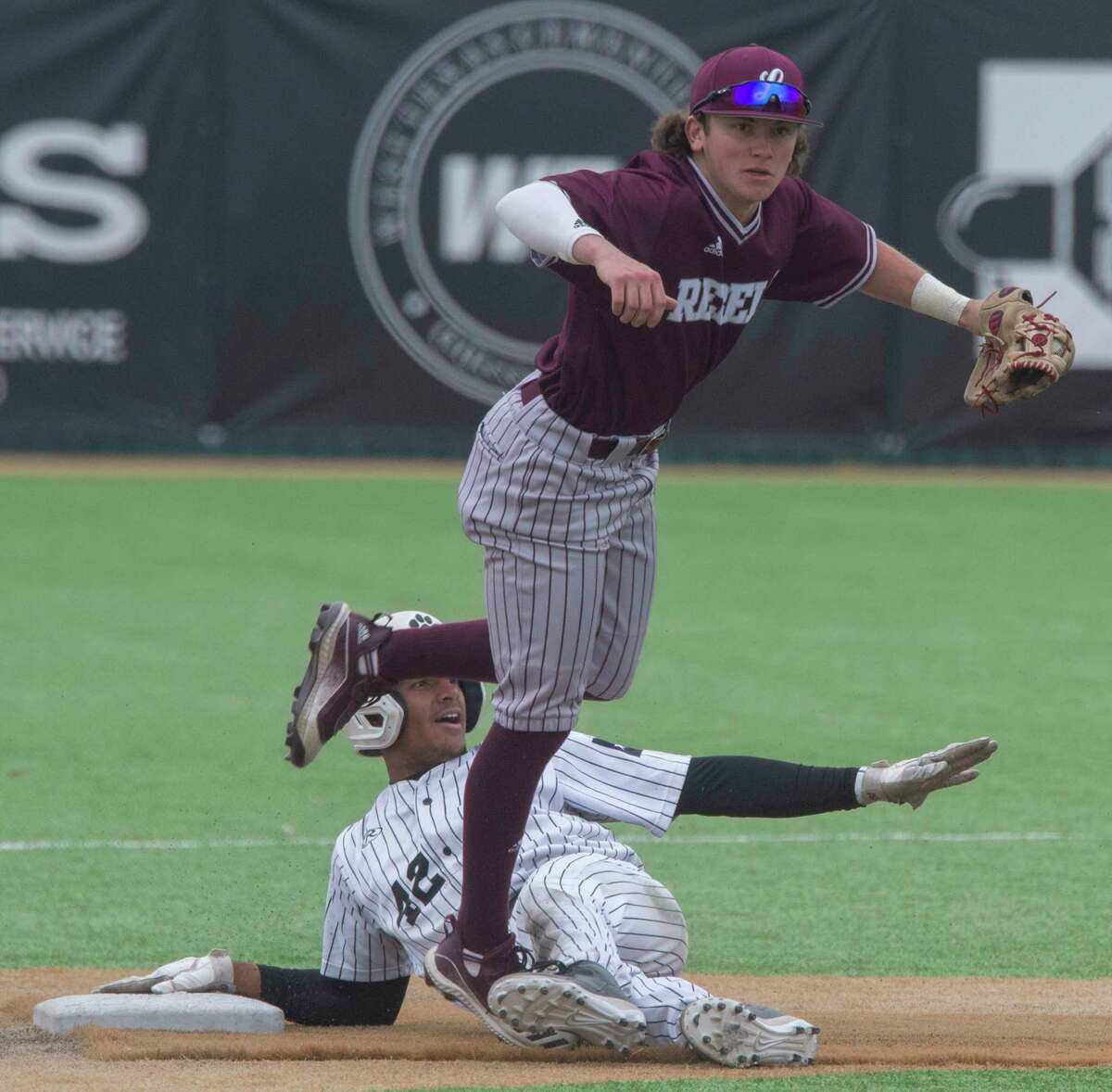 Lee High's Brayden Wynne leaps over Permian's Teo Banks after making the tag for an out at second 04/13/21 at McCanlies Field in Odessa. Tim Fischer/Reporter-Telegram