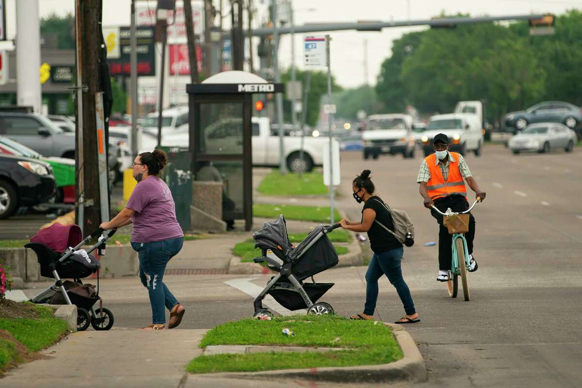 Pedestrians cross Hillcroft Avenue north of Bellaire Boulevard on Tuesday, April 13, 2021, in Houston. The city is set to begin work on Hillcroft that would take the eight-lane street down to six lanes, adding new bike lines and attempting to make the stretch of road more pedestrian friendly.