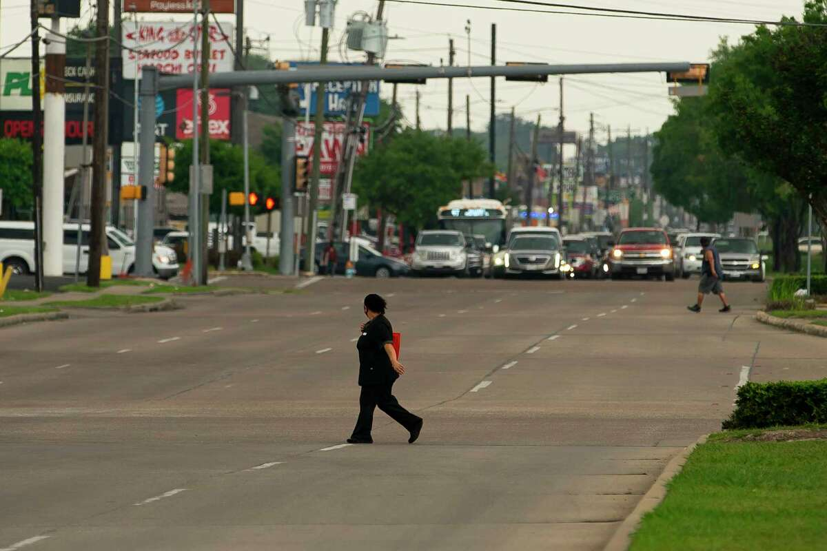 A pedestrians crosses Hillcroft Avenue north of Bellaire Boulevard on Tuesday, April 13, 2021, in Houston. The city is set to begin work on Hillcroft that would take the eight-lane street down to six lanes, adding new bike lines and attempting to make the stretch of road more pedestrian friendly.