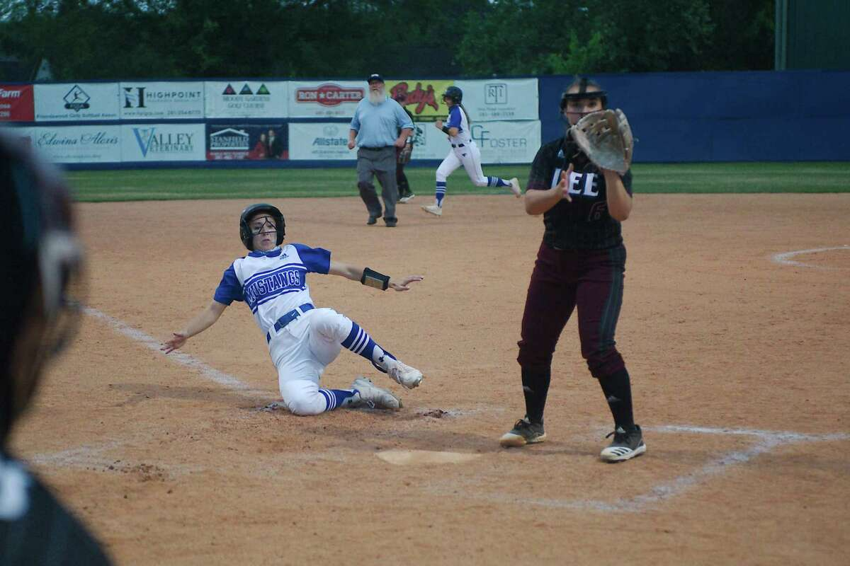 Friendswood's Halle Cordova (11) slides safely into home plate for a run against Baytown Lee Tuesday, Apr. 13 at Friendswood High School.