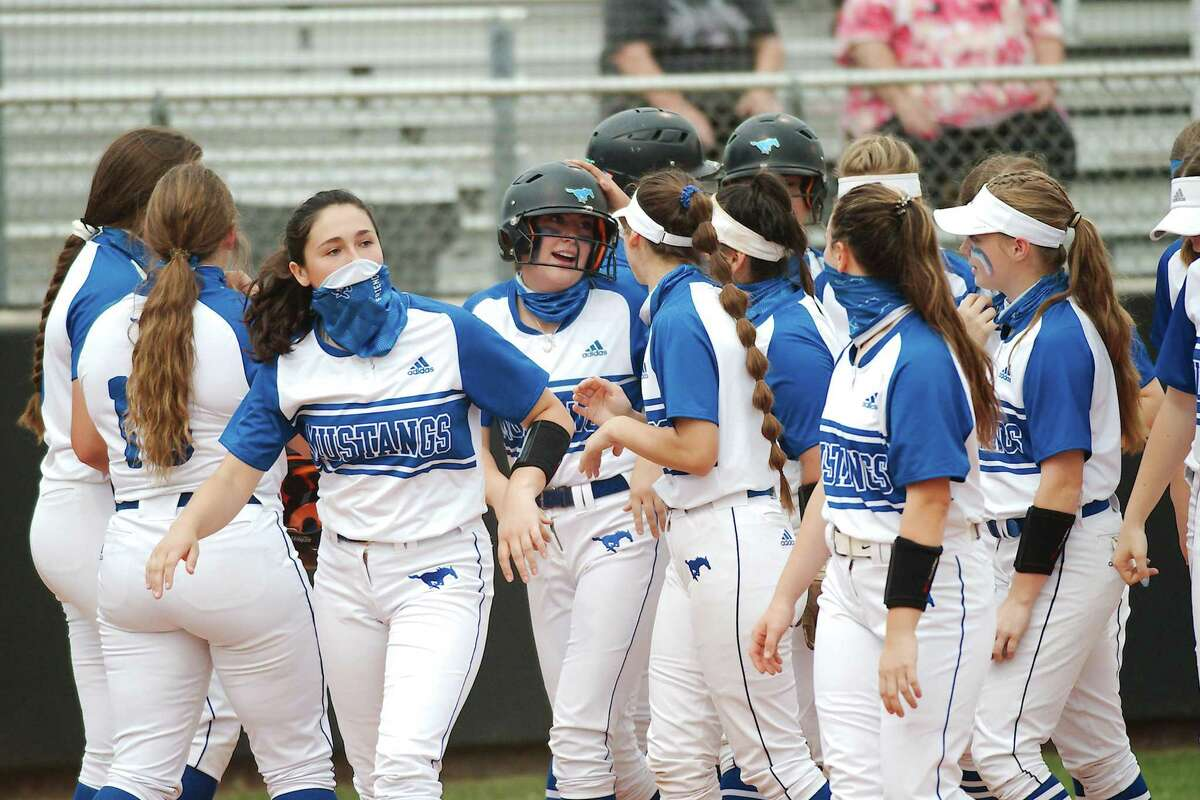 Friendswood's Alaina Schaefer (4) is swarmed by teammates after hitting a home run against Baytown Lee Tuesday, Apr. 13 at Friendswood High School.