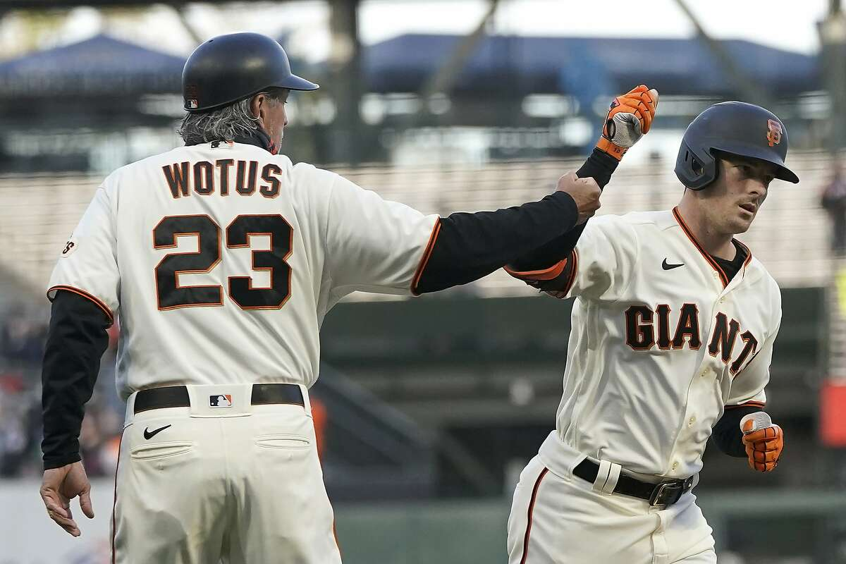San Francisco Giants' Mike Yastrzemski, right, is congratulated by third base coach Ron Wotus after hitting a two-run home run against the Cincinnati Reds during the first inning of a baseball game in San Francisco, Tuesday, April 13, 2021. (AP Photo/Jeff Chiu)