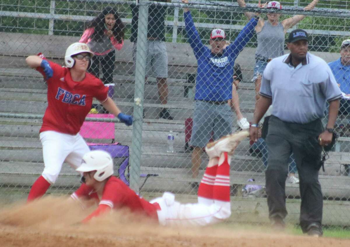 FBCA's Brayden Evans belly slides across home plate, scoring the winning run Tuesday night after Ryan Towe's basehit and the team down to their final out.