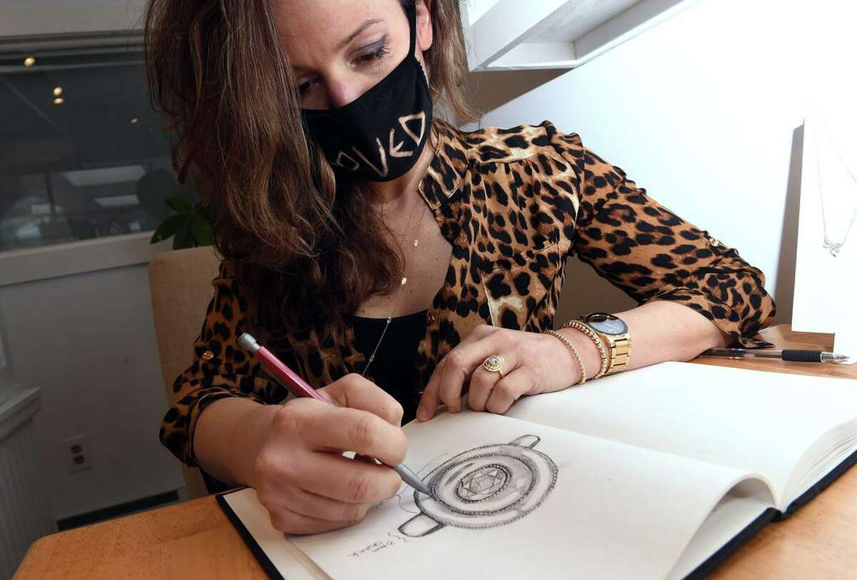Water Street Jewelers owner Daniela Balzano sketches a ring design at her store in Madison on April 1.