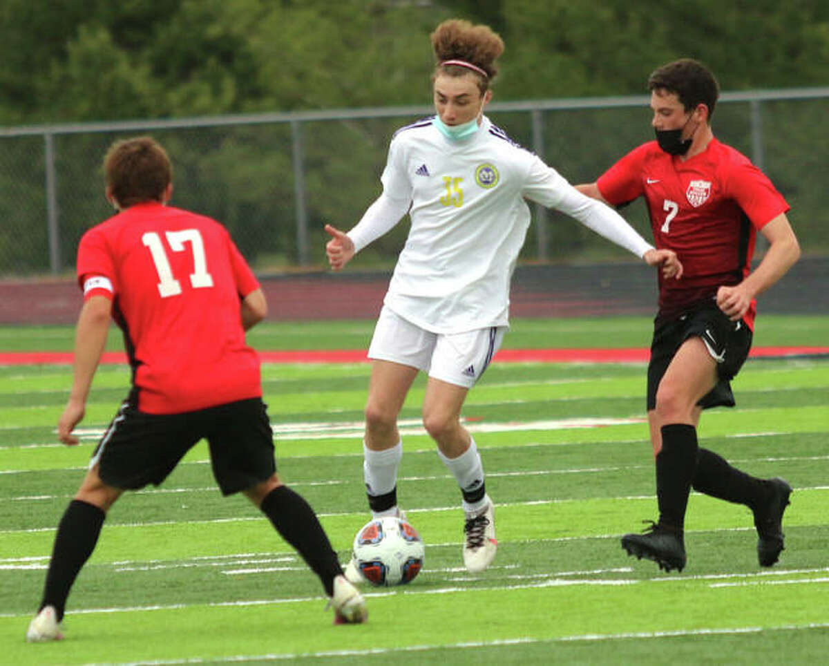 CM's Bryce Davis, center, scored a pair of goal Tuesday in his team's 4-2 loss to Triad. He is pictured earlier in the season against Triad in Troy, handling the ball between Triad's Eli Kraabel (17) and Cameron Ramirez.