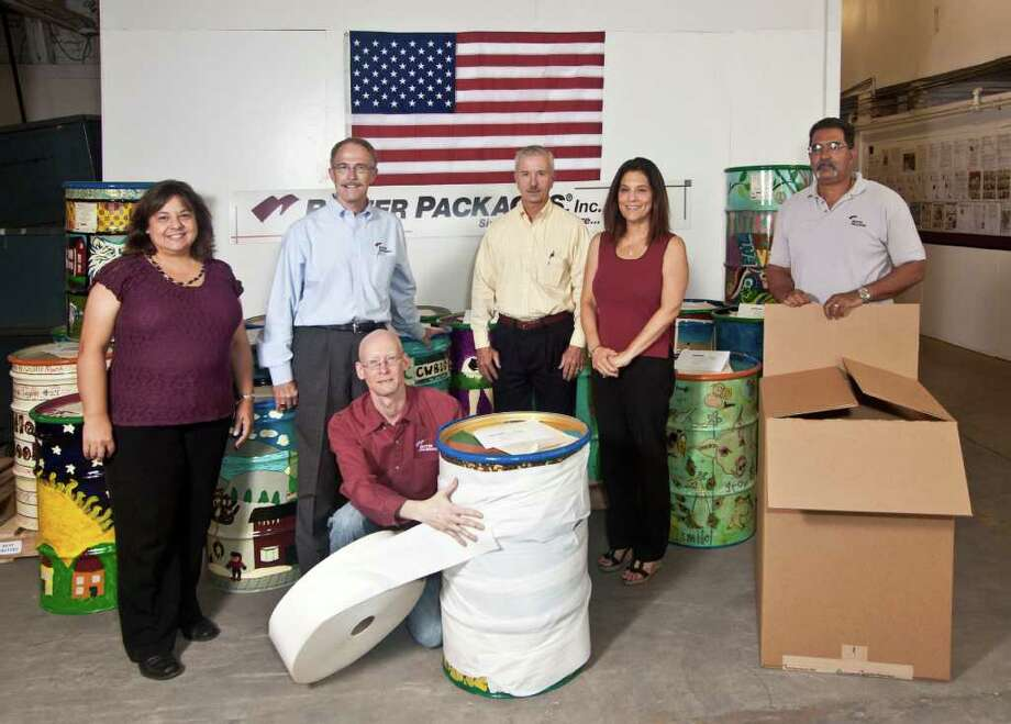 The Better Packages Team prepares the drums for the troops to be shipped overseas:  (back row, l-r) Mary Ann Miskowicz, Phil White, Paul Kromberg, Lynn Padell, Luis Alvarado, and (kneeling) Rick Kaliszewski. Photo: Contributed Photo / Connecticut Post Contributed