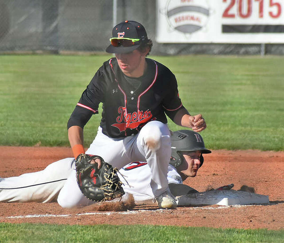 Edwardsville first baseman Riley Iffrig takes a pickoff throw while a Highland runner dives safely back to the bag during the first inning Tuesday at Glik Park in Highland.