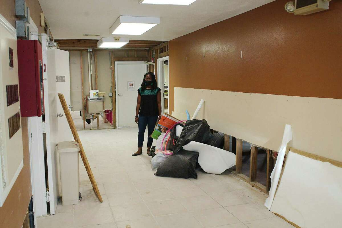 Bridge Over Troubled Waters Director Olivia Rivers stands in a hallway where water damage to the walls and floor is visible as after pipes broke during the recent hard freeze at the child care facility of Destiny Village Apartments .