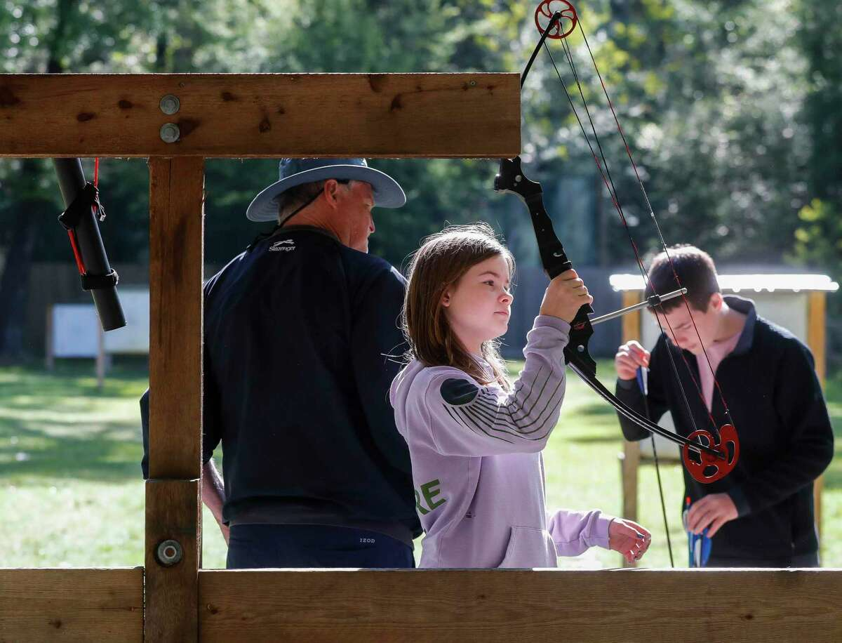 Audrey Carroll takes a compound bow off the rack as she, her siblings and her grandfather enjoy The Woodlands Township's archery range at Rob Fleming Park on Friday, April 2, 2021, in The Woodlands. Carroll's grandfather, a lifelong archer himself, spent the morning teaching his grandchildren the sport while visiting for the Easter weekend.