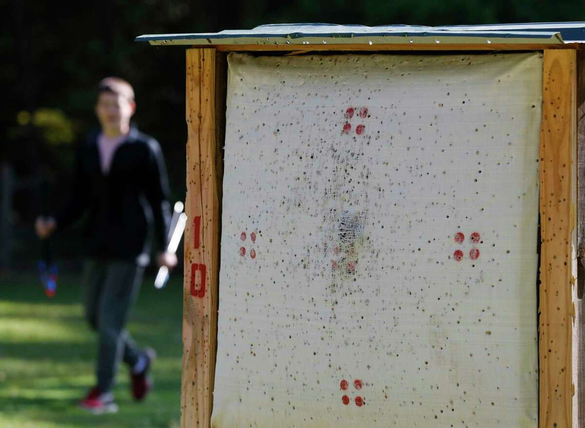 Nate Carroll passes by an archery target while he, his siblings and his grandfather enjoy The Woodlands Township's archery range at Rob Fleming Park on Friday, April 2, 2021, in The Woodlands. Carroll's grandfather, a lifelong archer himself, spent the morning teaching his grandchildren the sport while visiting for the Easter weekend.