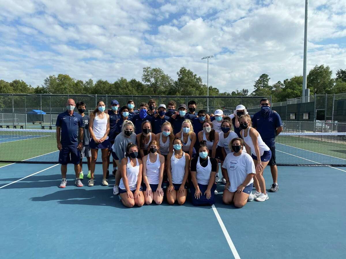 Kingwood coach Greg Dwyer (far left) poses with his tennis teams after a match.