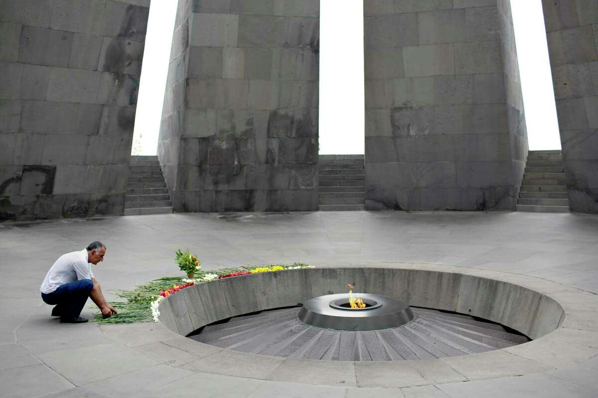 """A man places flowers at the eternal flame in the Armenian Genocide memorial complex in Yerevan, Armenia, on Aug. 11, 2018. After the recent """"velvet revolution,"""" the sense of a new era in Armenia is palpable. (Danielle Villasana/The New York Times)"""