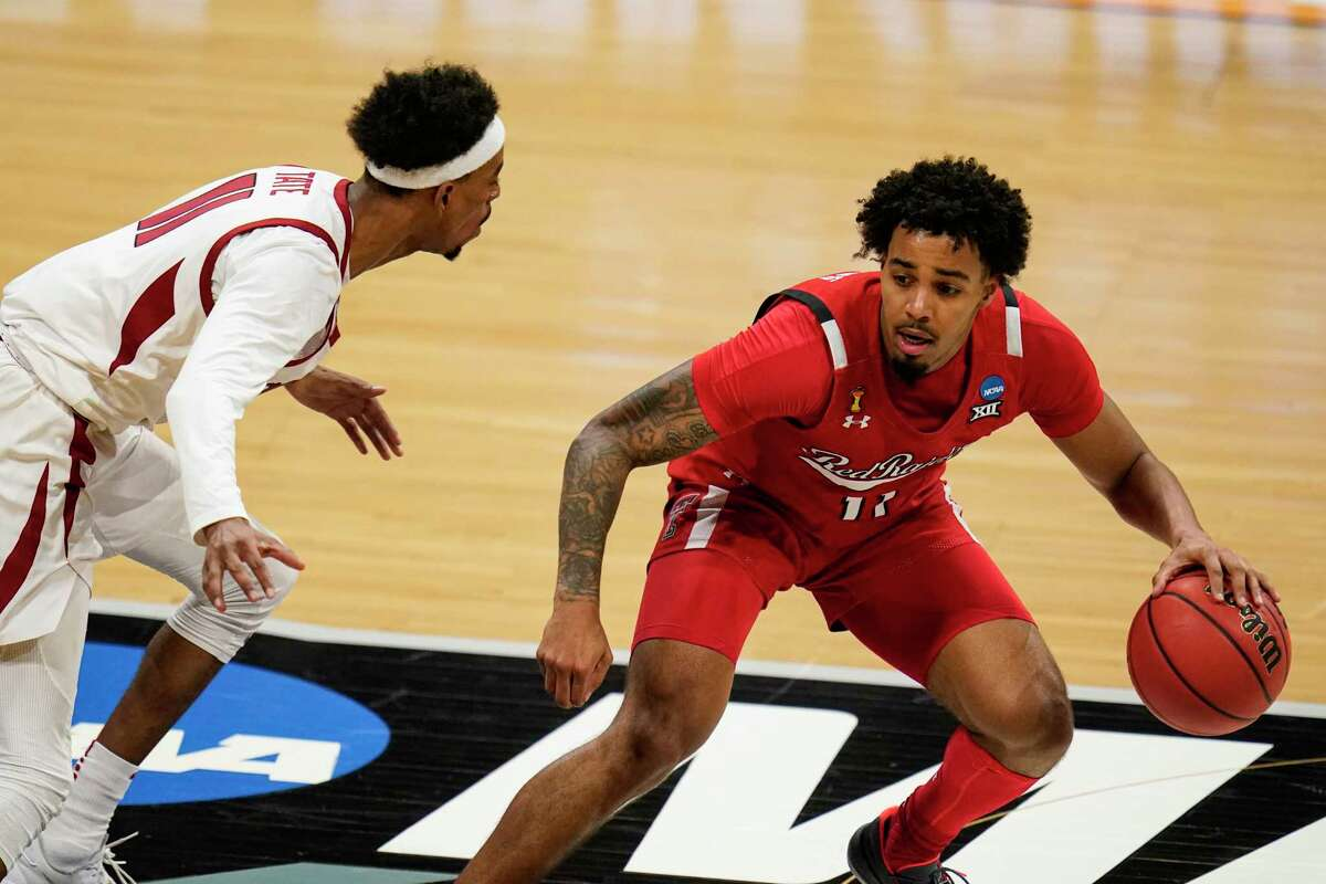 Texas Tech guard Kyler Edwards (11) drives on Arkansas guard Jalen Tate (11) in the first half of a second-round game in the NCAA men's college basketball tournament at Hinkle Fieldhouse in Indianapolis, Sunday, March 21, 2021. (AP Photo/Michael Conroy)