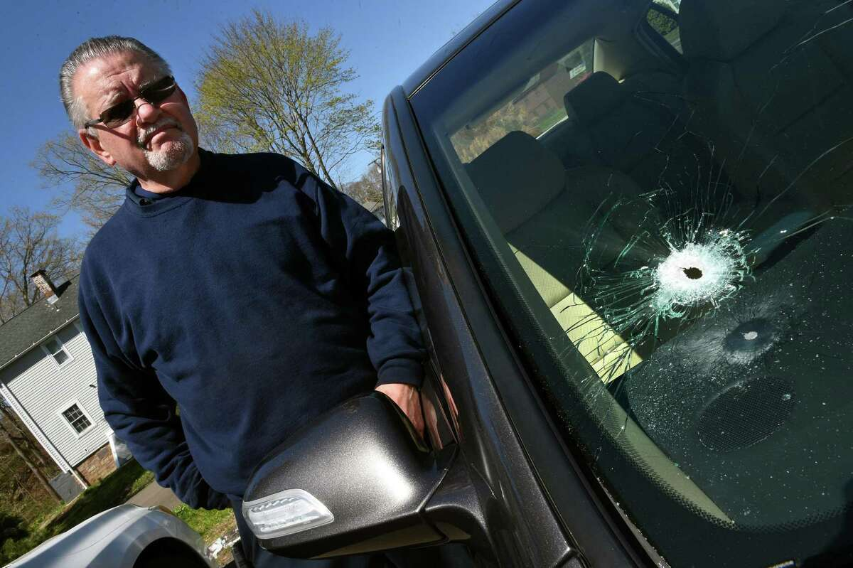 Larry Stoup, owner of Pepe's Service Station, standing next to a customer's Acura with a bullet hole in the windshield.