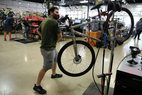 Bike World employee Kevin Connor prepares a bike for a customer to test ride.