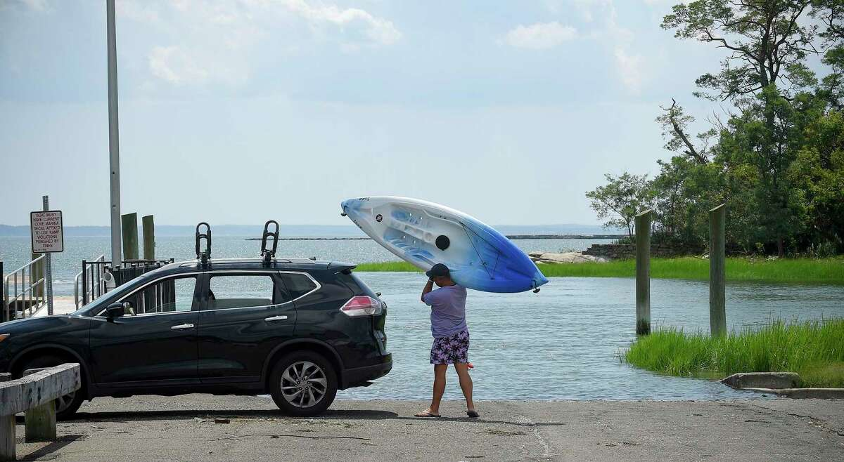 A man shoulders his kayak in August 2020 at Cove Island Marina in Stamford, Conn.