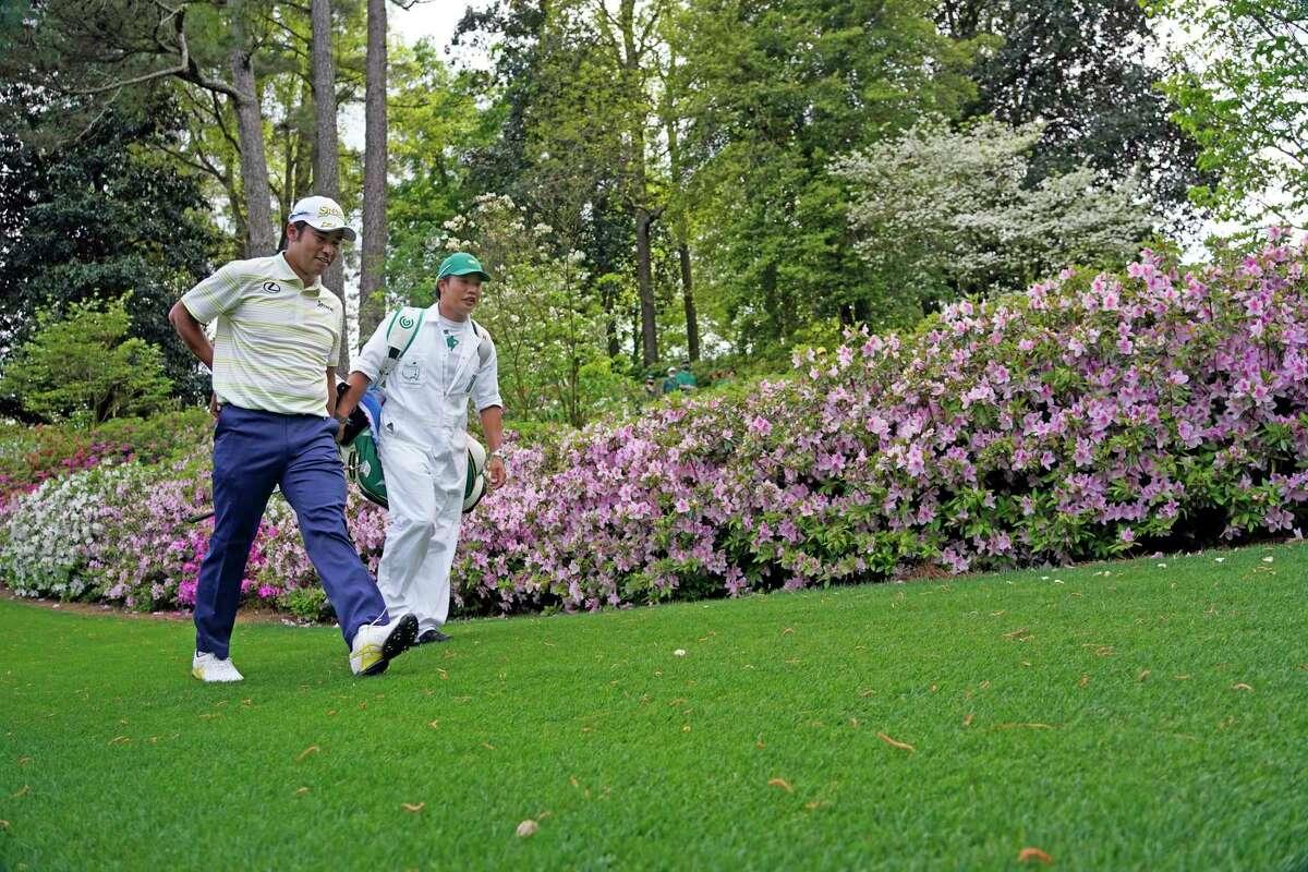 Hideki Matsuyama, of Japan, left, and his caddie, Shota Hayafuji walk toward the sixth green during the Masters golf tournament Sunday, April 11, 2021, in Augusta, Ga.