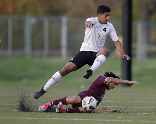 Porter's Edwin Morales (11) leaps over Magnolia's Alberto Alzaman (5) as he makes a tackle during the first period of a high school bi-district playoff soccer match at Montgomery High School, Thursday, March 25, 2021, in The Montgomery. Photo: Jason Fochtman/Staff Photographer / 2021 © Houston Chronicle
