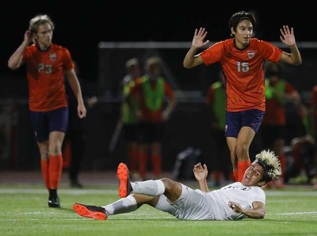 The Woodlands'€™ Juan Camilio Lopez (16) reacts after being hit from behind by Bridgeland's Ian Inigo (15) during the first period of a high school girls soccer playoff match at Klein Oak High School, Tuesday, March 30, 2021, in Spring. Photo: Jason Fochtman/Staff Photographer / 2021 © Houston Chronicle