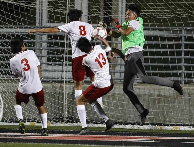 Splendora goalie Ivan Olguin (5) makes a stop against Huffman's Antonio Calzada (8) and Oscar Botello, Jr. (13) during the first overtime period of a Region III-4A championship match at Randall Reed Stadium, Friday, April 9, 2021, in New Caney. Huffman defeated Splendora 1-0. Photo: Jason Fochtman/Staff Photographer / 2021 © Houston Chronicle
