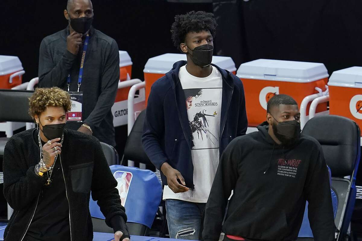 Injured Golden State Warriors' Kelly Oubre Jr., bottom left, James Wiseman, middle, and Eric Paschall watch during the second half of an NBA basketball game against the Denver Nuggets in San Francisco, Monday, April 12, 2021. (AP Photo/Jeff Chiu)