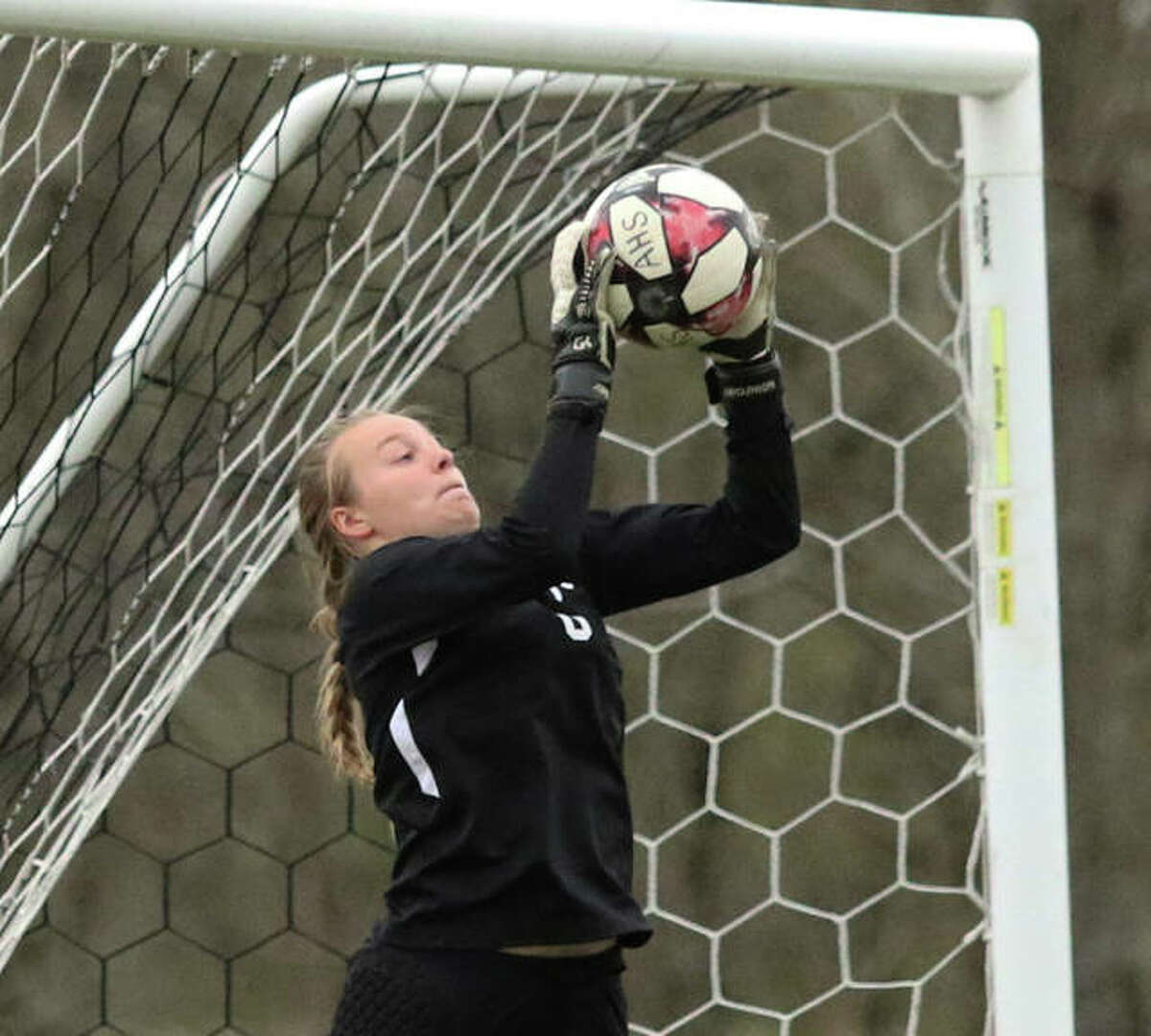 Alton goalie Addison Miller makes a save during a 2019 game. Miller, now a senior, is one of three senior captains on the AHS team this season. The Redbirds, like all Illinois high school girls soccer teams, are returning this week for the first time since 2019 after the 2020 season was cancelled because of the pandemic.