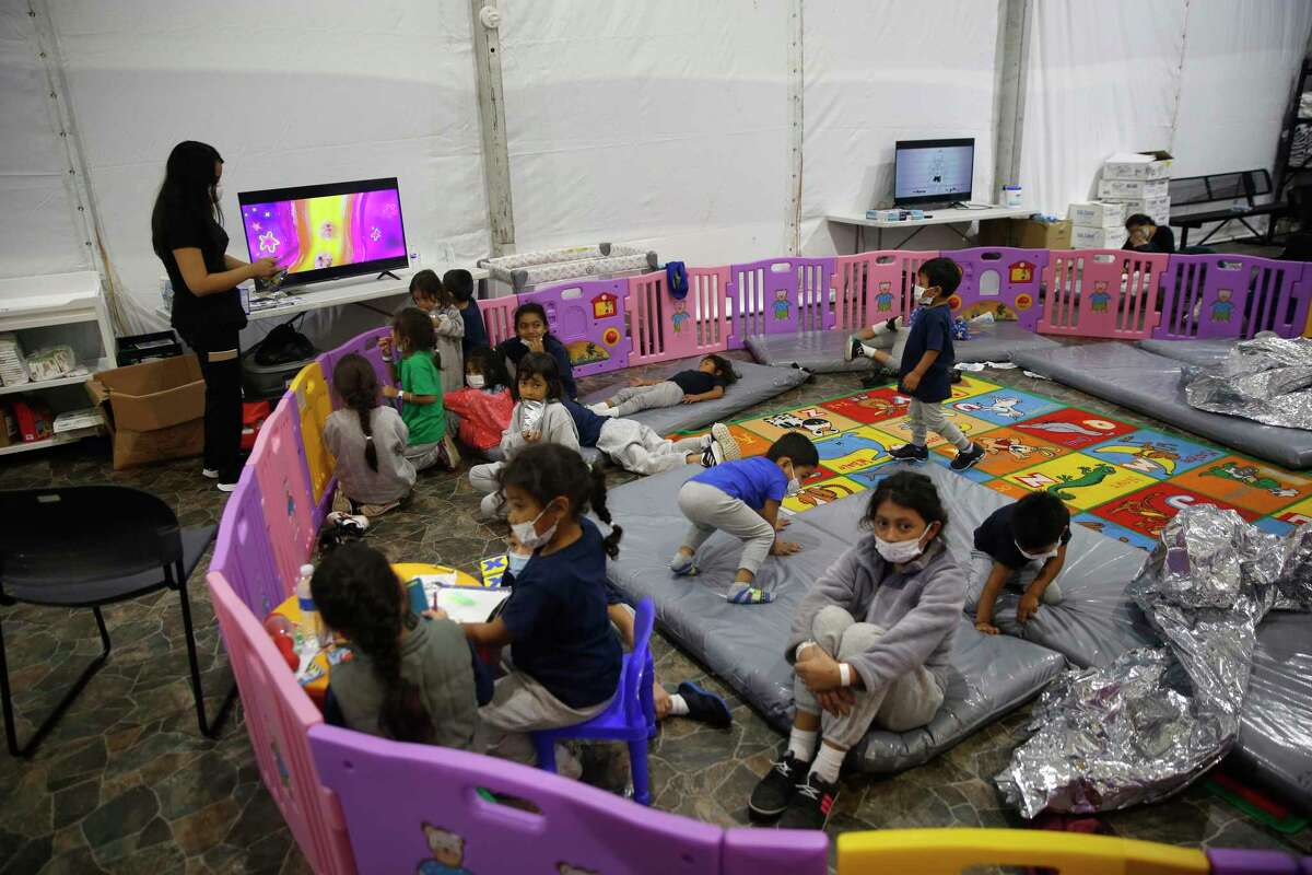 DONNA, TEXAS - MARCH 30: Monitored by a caretaker, young unaccompanied migrants, ages 3-9, watch TV inside a play pen in the Department of Homeland Security holding facility on March 30, 2021 in Donna, Texas. The Donna location is the main detention center for unaccompanied children coming across the U.S. border in the Rio Grande Valley. The youngest of the unaccompanied minors are kept separate from the rest of the detainees. The Biden administration has just allowed journalists inside its main detention facility at the border for migrant children. It is an overcrowded tent structure where more than 4,000 kids and families are kept in pods, with the youngest kept in a large play pen with mats on the floor for sleeping. (Photo by Dario Lopez-Mills - Pool/Getty Images) *** BESTPIX ***