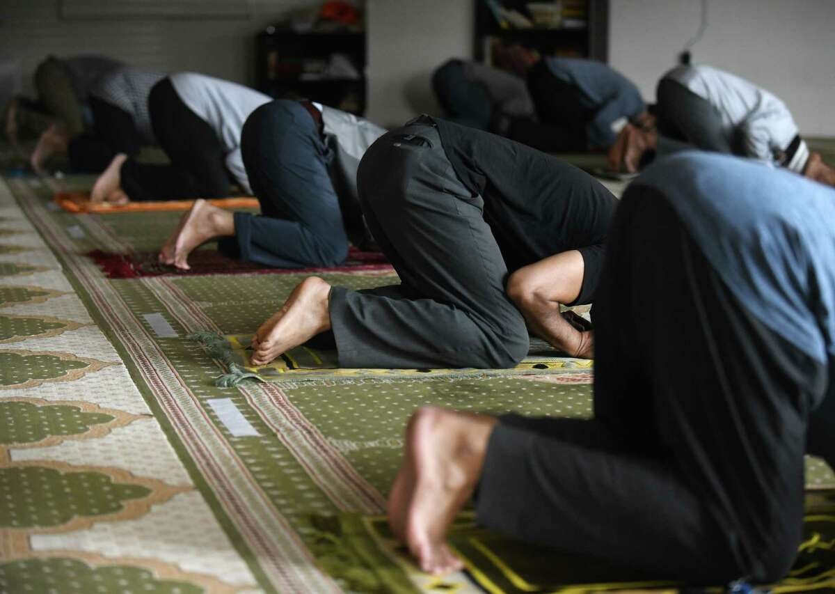 Men pray during the early-afternoon jamaat during the holy month of Ramadan at Stamford Islamic Center in Stamford, Conn. Wednesday, April 14, 2021. The mosque was closed due to COVID last year during Ramadan, but is open this year with safety precautions in place. Capacity has been limited from 130 to 55 and worshippers are expected to bring their own prayer mats, wear masks, and stay six feet apart from one another.
