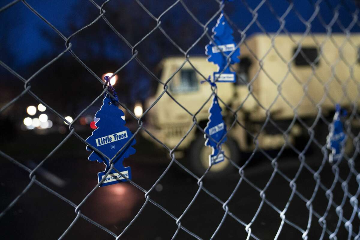 Demonstrators hang car air fresheners from a perimeter fence outside the Brooklyn Center Police Department to protest the shooting death of Daunte Wright.
