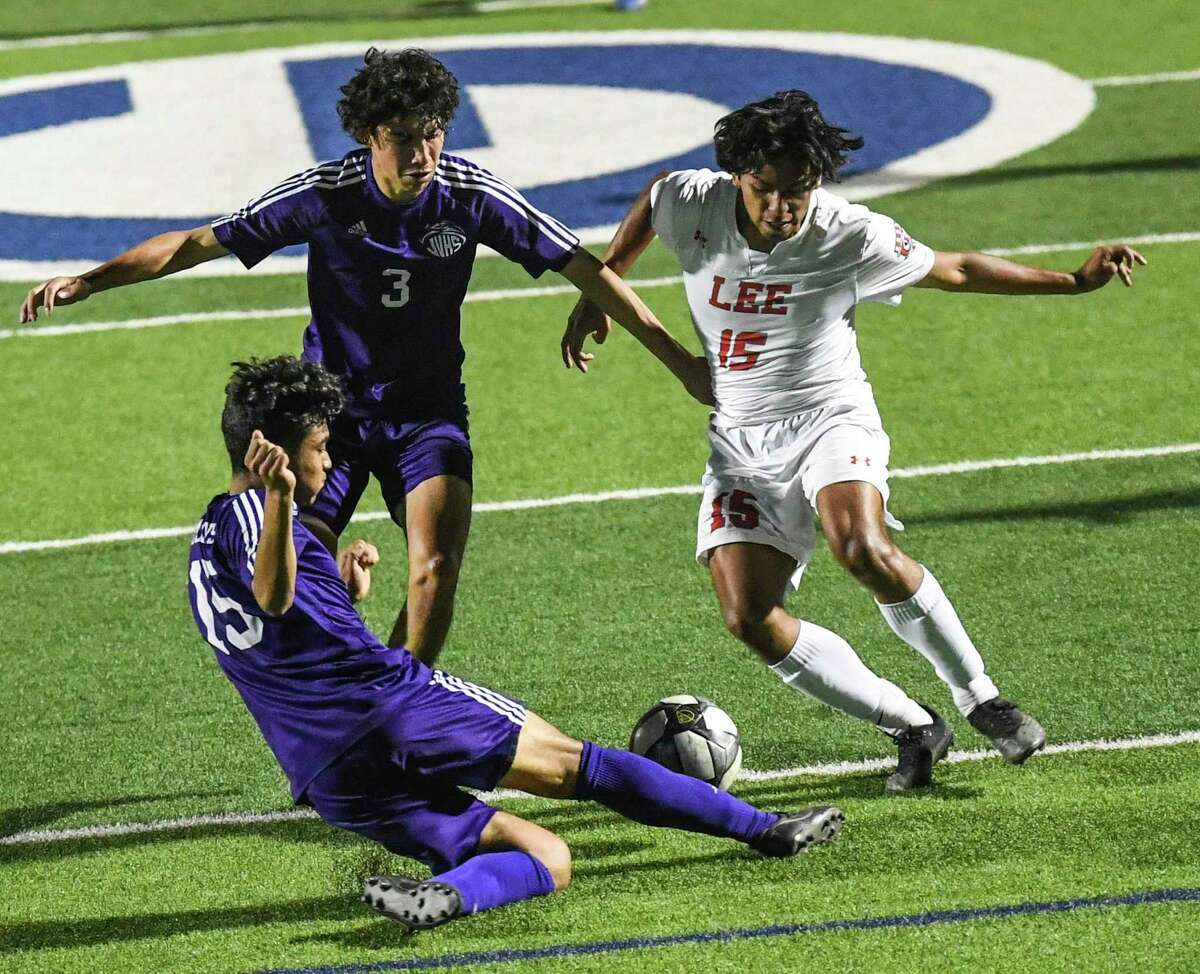 Ozzy Espitia, right, of LEE attempts to work the ball toward the goal as Jose Bejarano (3) and Juan Reyes (15) of Jersey Village defend during the Class 6A state semifinal in Georgetown on Tuesday, April 13, 2021.