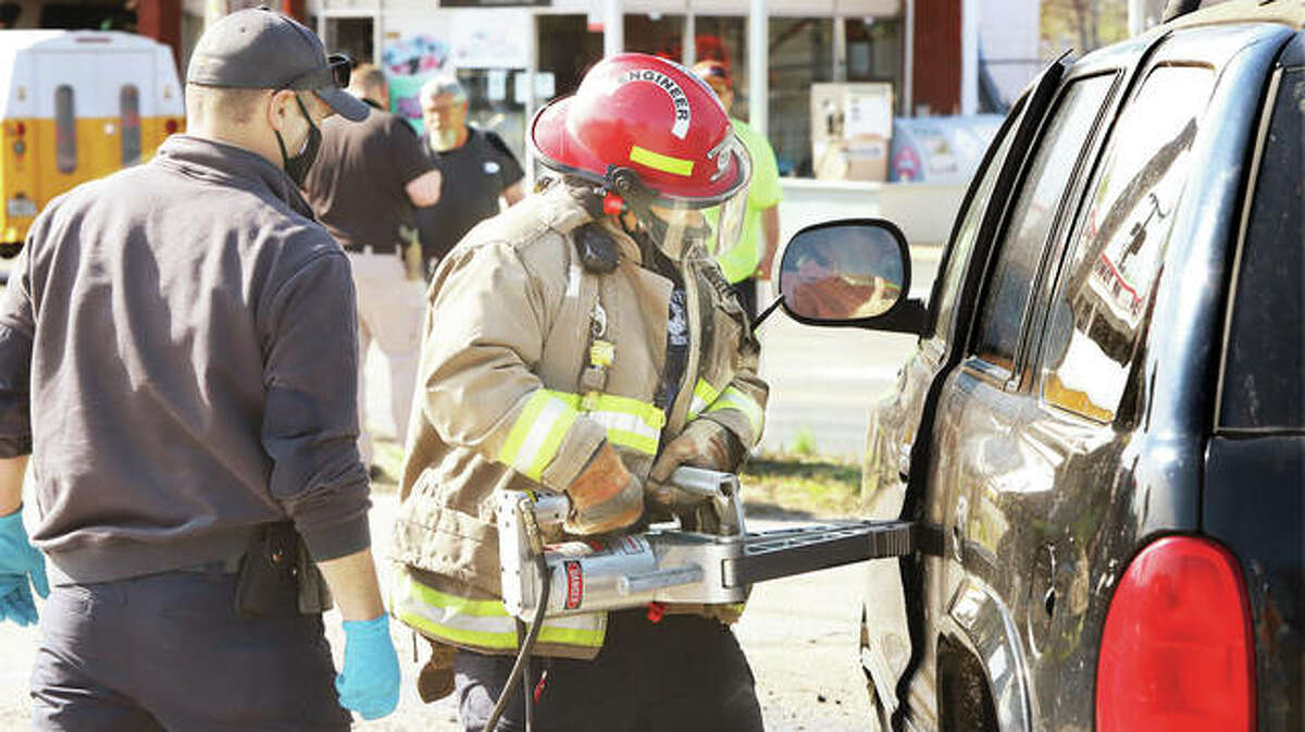 A Wood River firefighter uses a hydraulic rescue tool Wednesday to pry open the door of Dodge Durango after it crashed head-on with a Jeep Patriot on Edwardsville Road at George Street just before 10 a.m. Once the driver was extricated, the Alton Memorial Ambulance he was in struck a police car. Minor damage was caused to the ambulance and squad car; both the Jeep and Durango received major damage.