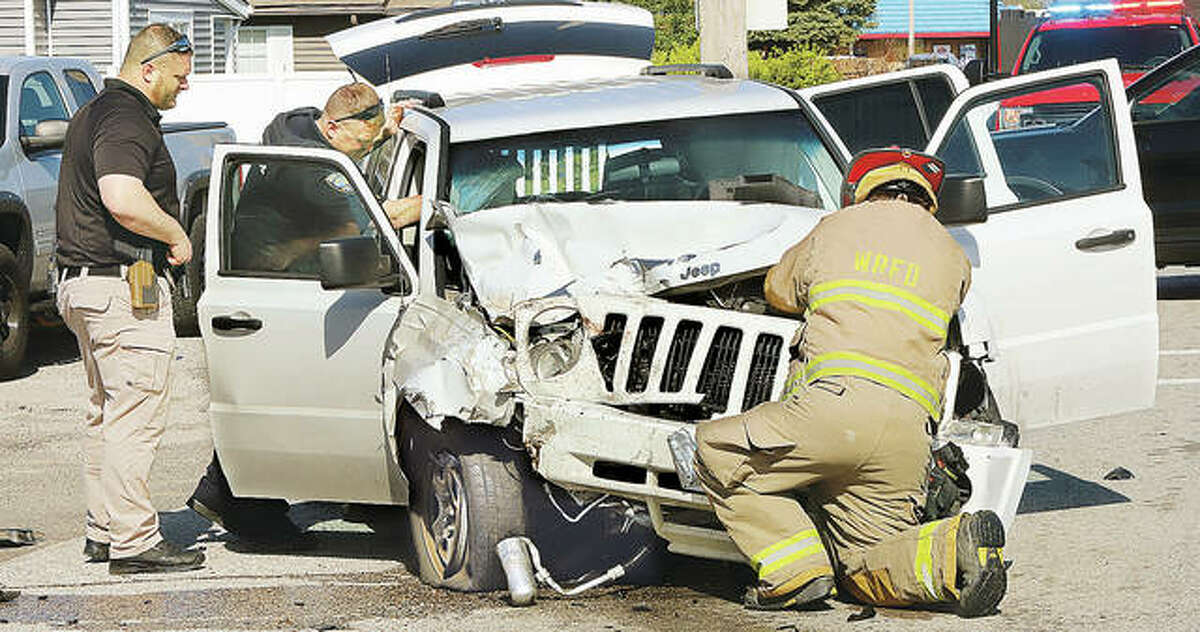 A Wood River firefighter works to disconnect a Jeep Patriot's battery following a Wednesday morning accident.
