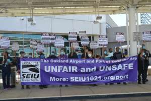 Custodians protest outside the Southwest terminal at Oakland International Airport on Wednesday, April 14, 2021.