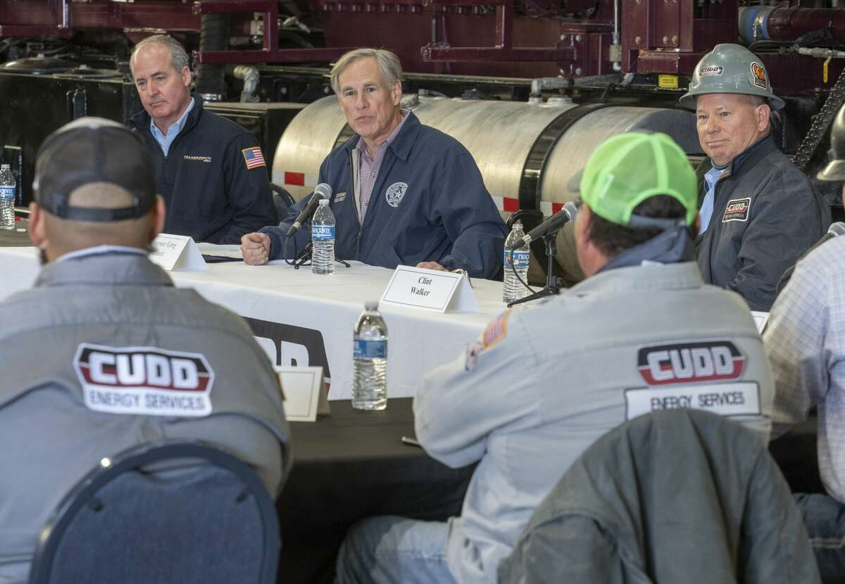 Texas Governor Greg Abbott, center, leads a roundtable discussion with Travis Stice, left, in this Reporter-Telegram file photo from Jan. 28.