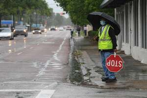A crossing guard waits to assist Pietzch-MacArthur students across Highland Avenue in a late afternoon rainfall Wednesday. Photo made Wednesday, April 14, 2021 Kim Brent/The Enterprise