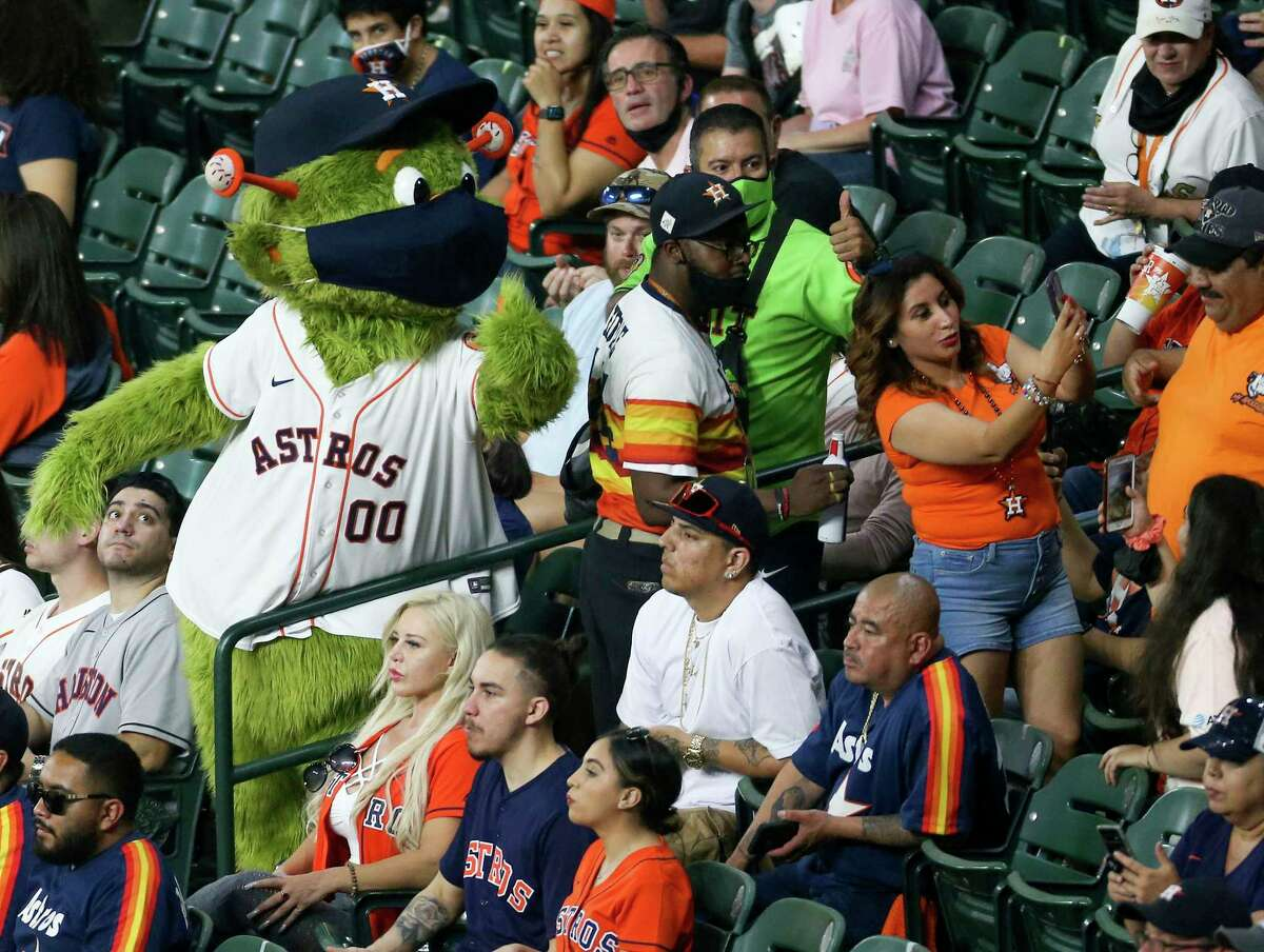 Despite recommendations to wear masks and socially distance, Astros mascot Orbit was one of the few seen wearing a mask in this section during the home opener against Oakland Athletics at Minute Maid Park in Houston on Thursday, April 8, 2021. More than 21,000 people attended the game.