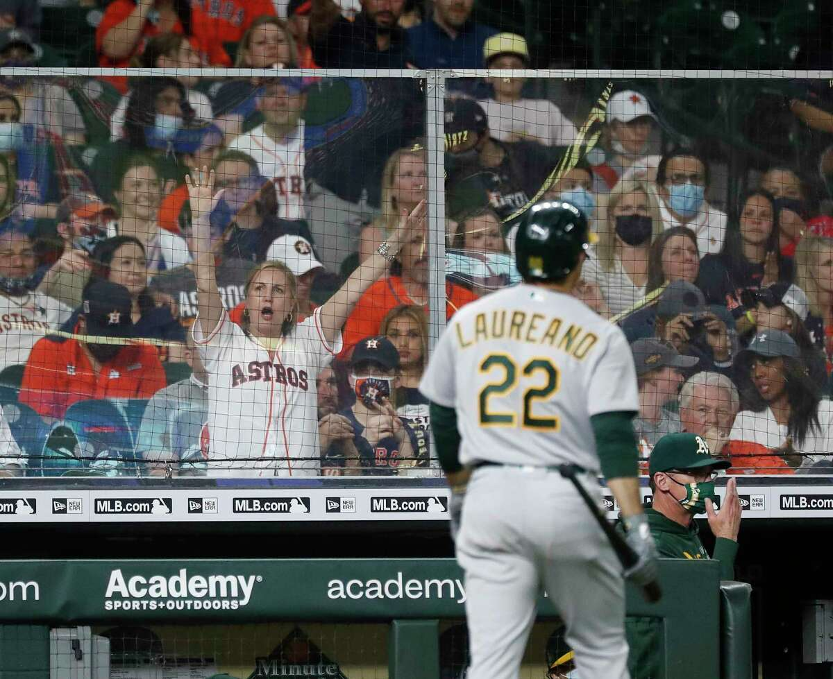 A Houston Astros fan cheers behind a sheet of plexiglass as Oakland Athletics Ramon Laureano (22) walks back to the dugout after striking out against Houston Astros relief pitcher Bryan Abreu during the eighth inning of an MLB baseball game at Minute Maid Park, in Houston, Friday, April 9, 2021. The Astros are averaging more than 19,000 fans per home game.