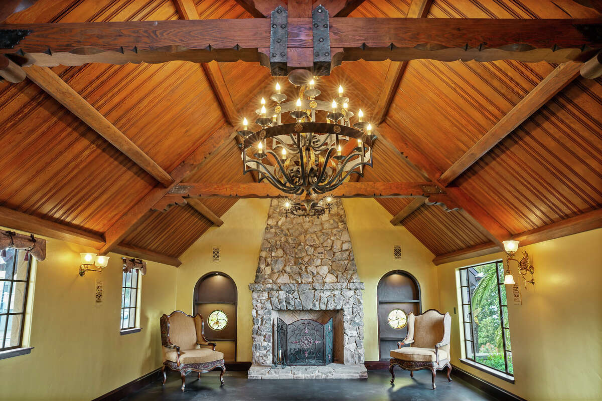 The soaring Great Room features a hearth and wood paneled ceiling.