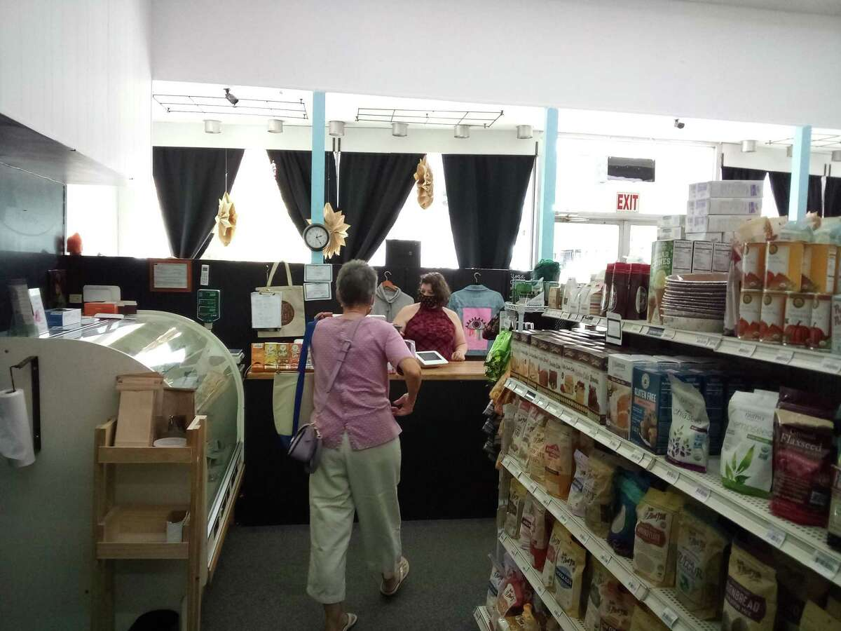 Rooted Market Manager Nicole Starr waits on a customer at the counter.