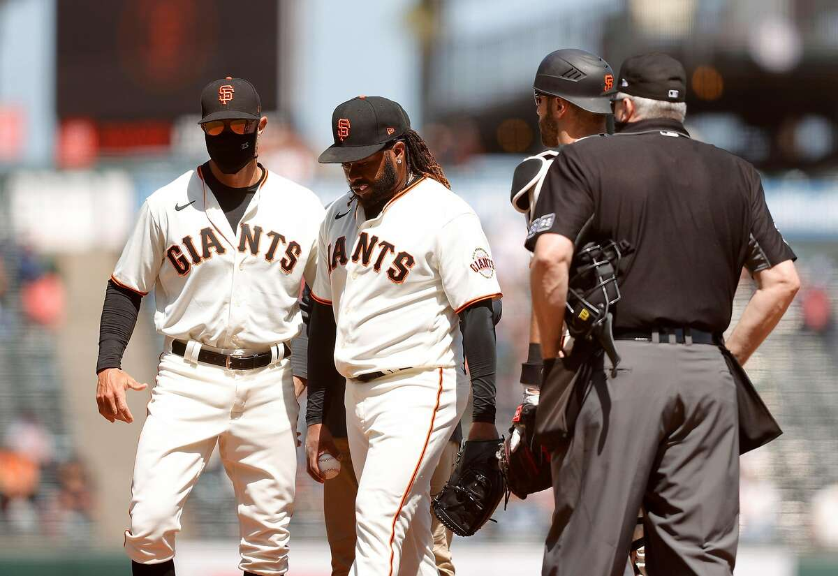 Johnny Cueto (center) removes himself in the sixth inning, with help from Gabe Kapler, after experiencing tightness.