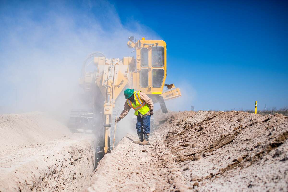 Workers with LOS's Oilfield Services cut a trench that will be used for a liquid transfer pipeline in the oilfield.