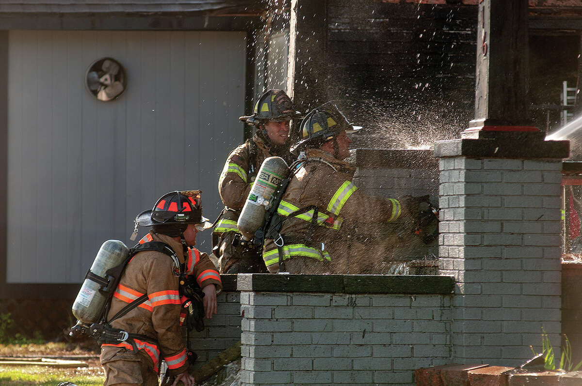 Firefighters battle a blaze Wednesday at an East College Avenue house that destroyed one structure and spread to one of the walls of a nearby restaurant.