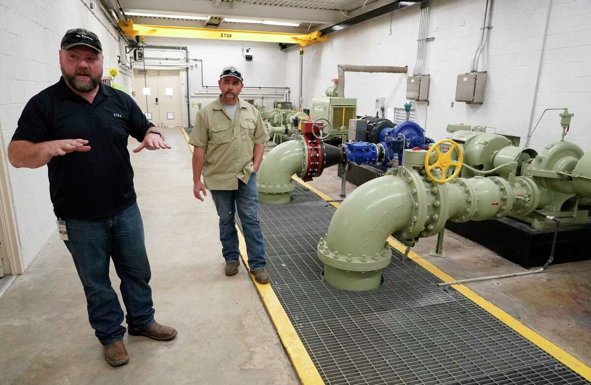 Jason Williams, operation manager, left, and Jacob Everett, chief maintenance technician, right, talk in the San Jacinto River Authority booster pump room at Water Plant No. 1 Wednesday, March 17, 2021 in The Woodlands.