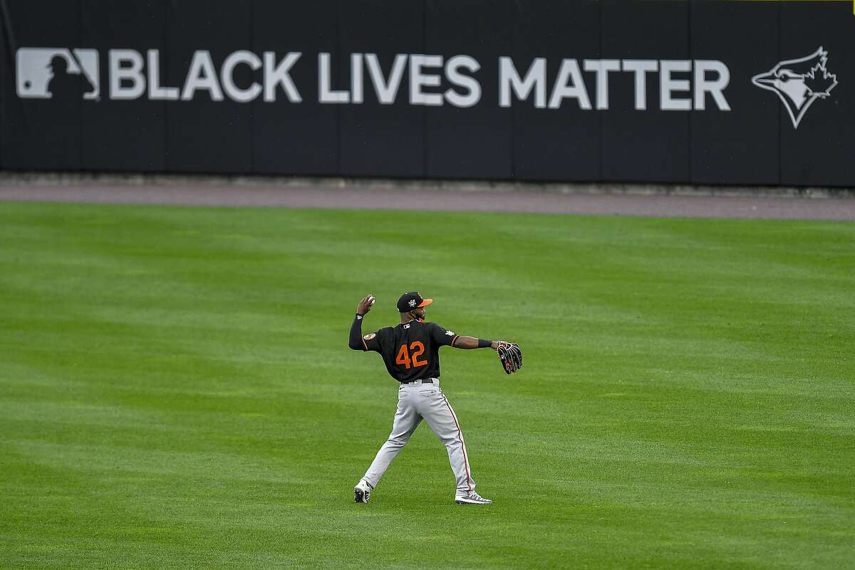 A Baltimore Orioles player warms up in the outfield before a baseball game against the Toronto Blue Jays in Buffalo, N.Y., Friday, Aug. 28, 2020. All players and coaches wore No. 42 uniforms in honor of Jackie Robinson Day around the league. (AP Photo/Adrian Kraus)
