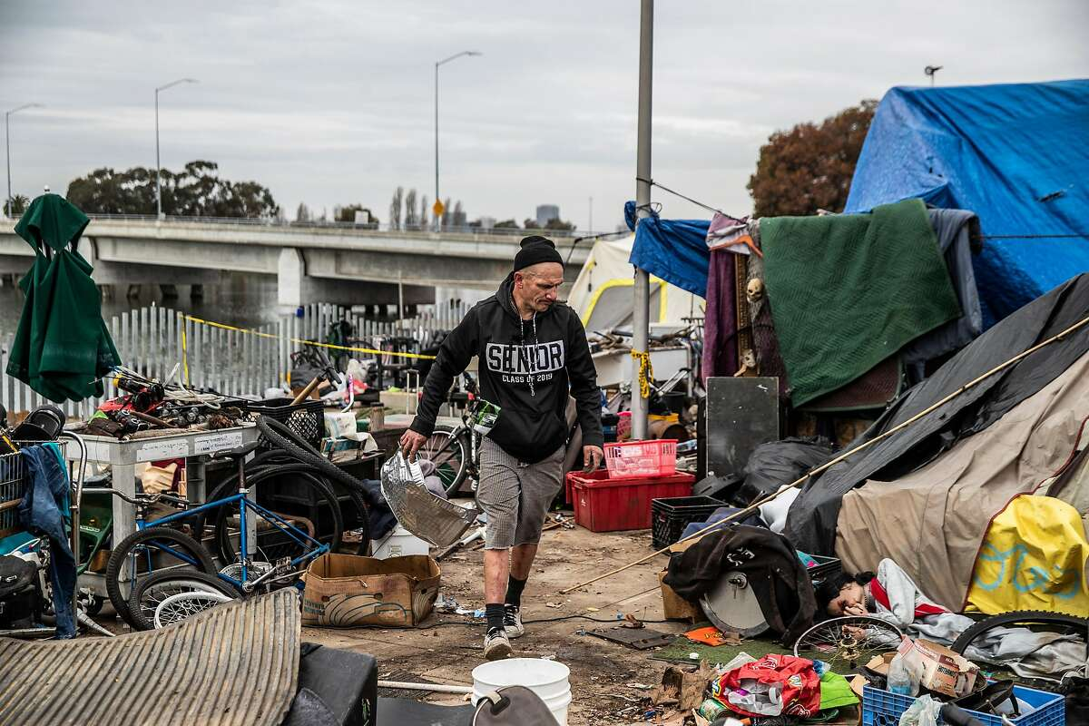 Mike Chastin, who is unemployed and living at a homeless encampment at Union Point Park for five years, cleans up his space ahead of a planned site clearing by the city of Oakland on Feb. 9.