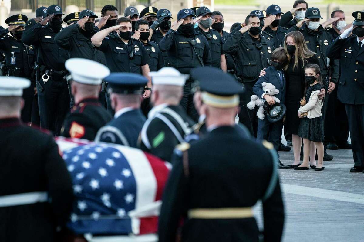 WASHINGTON, DC - APRIL 13: Family members of U.S. Capitol Police Officer William Evans, including Mrs. Shannon Terranova, their 9-year-old son Logan, and 7-year-old daughter Abigail watch his coffin being carried by a Joint Service of Honor Guard the steps of the Capitol's Eastern Front after lying in honor in the Rotunda on April 13, 2021 in Washington, DC.  Evans was killed and another injured after a man rammed through security and crashed into a barrier at the complex that forced him to lock down less than three months after the mob riot at Congress.  (Photo by Jabin Botsford-Pool / Getty Images)