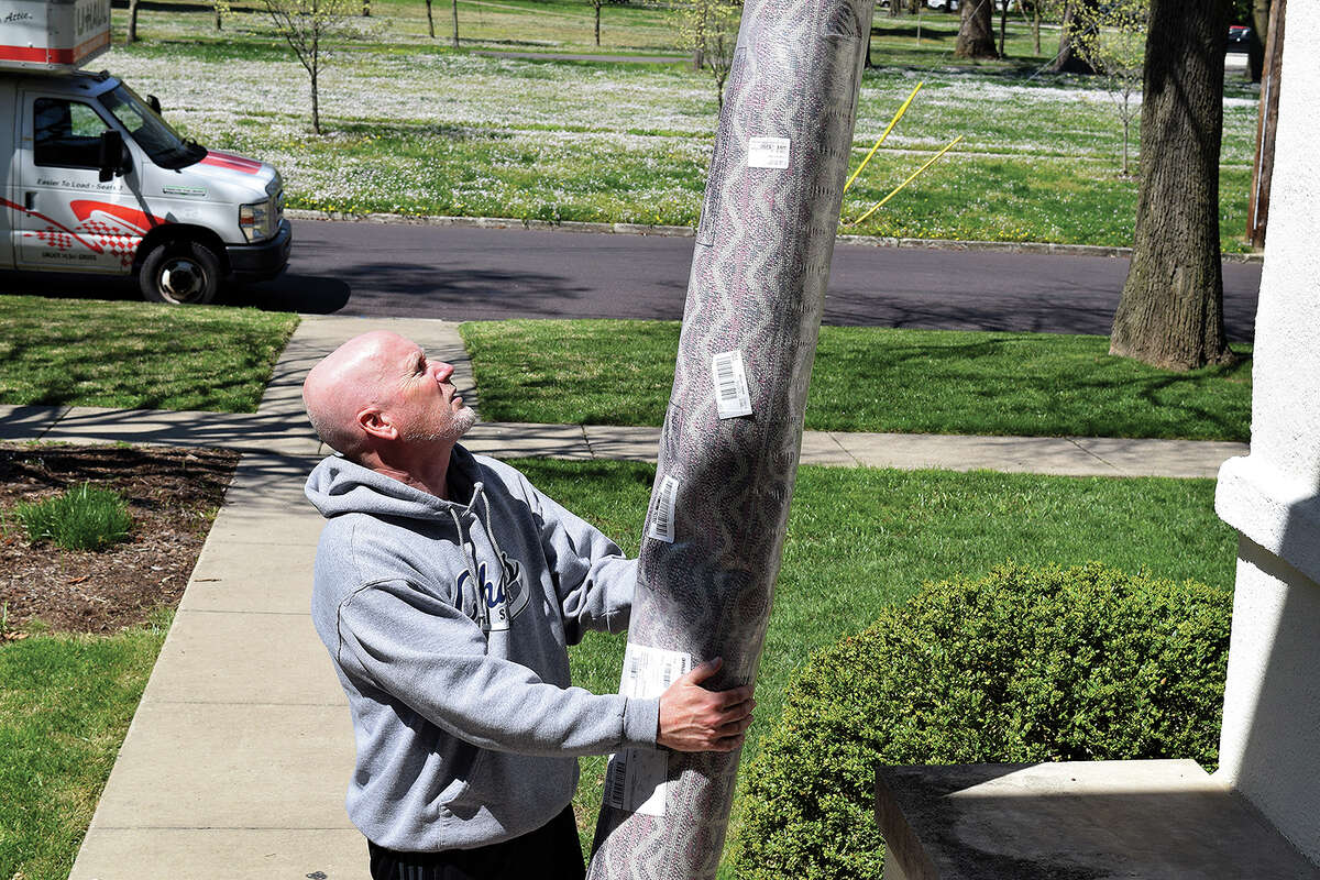 Incoming Beardstown Superintendent Michael Smith carries a rug into his new home Wednesday.