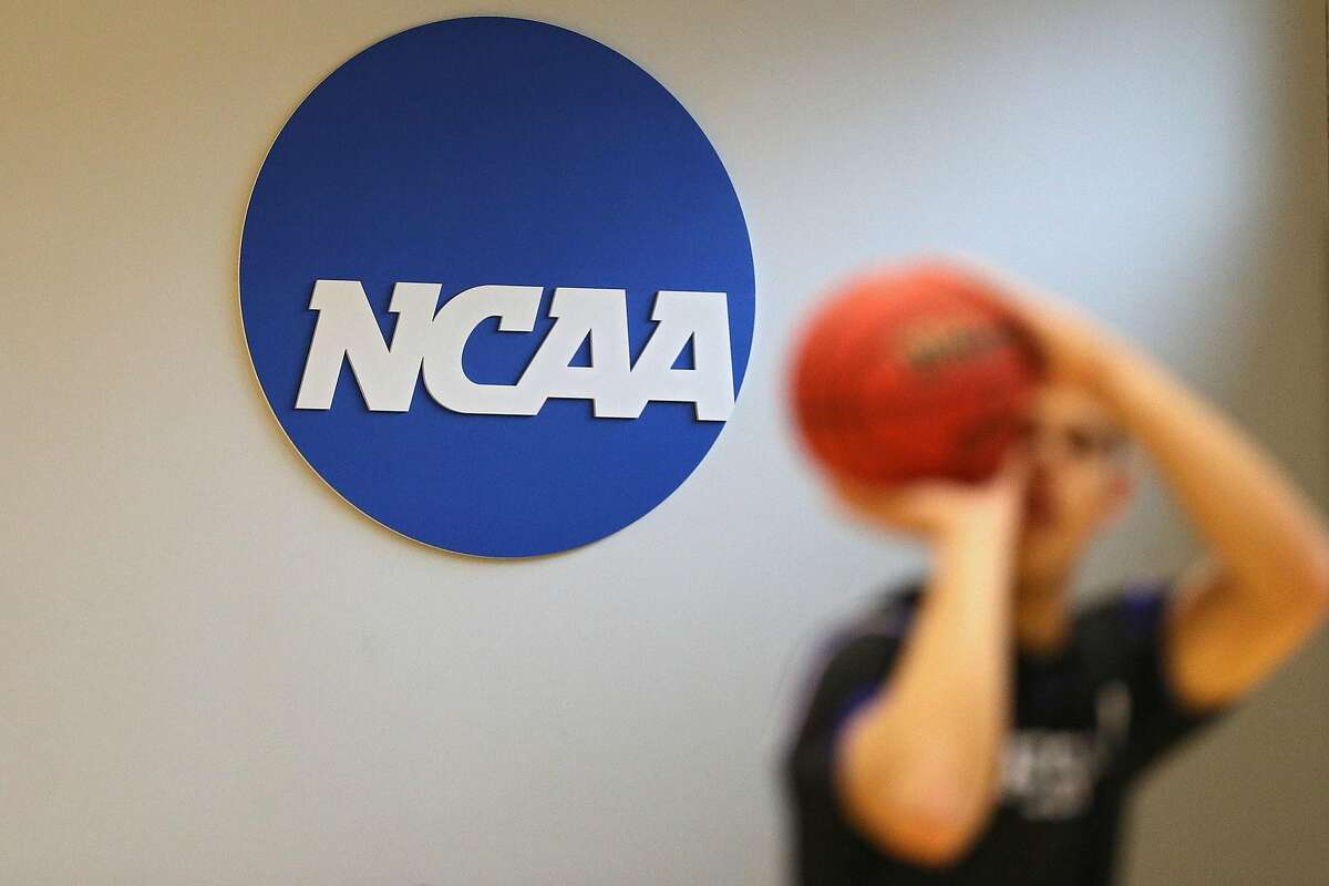 The NCAA logo is seen on the wall as Yeshiva players warmup prior to a game against Worcester Polytechnic Institute at Johns Hopkins University on March 6, 2020 in Baltimore, Maryland. The NCAA Board of Governors said it would consider pulling championships from states that pass bills banning transgender athletes from participating in women's and girl's sports. (Patrick Smith/Getty Images/TNS)